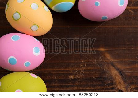 A group of colorful easter eggs on a wooden plank background