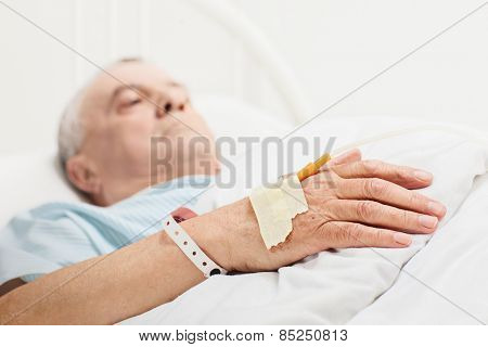 Sick senior lying in a hospital bed with iv drip attached on his hand with the focus on the iv set isolated on white background