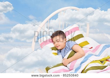 Cute little boy sleeping on a bed in the clouds