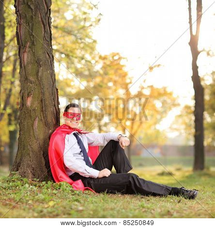 Joyful man in superhero outfit sitting in a park shot with tilt and shift lens