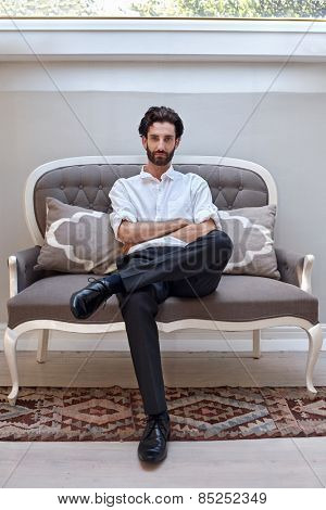 portrait of serious handsome man sitting on a sofa couch chair at home