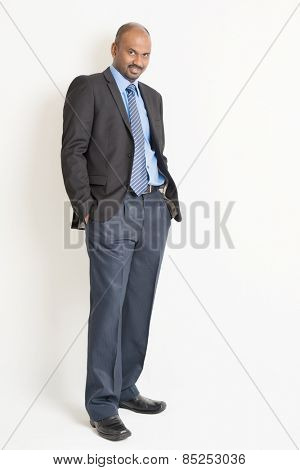 Full length Indian businessman in formal suit looking at camera, on plain background.
