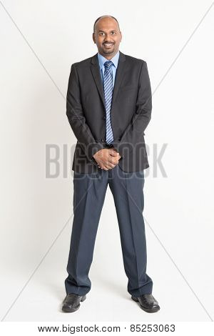 Full length friendly Indian businessman in formal suit looking at camera, standing on plain background.