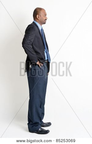 Full length profile view Indian businessman in formal suit looking at blank copy space, on plain background with shadow.