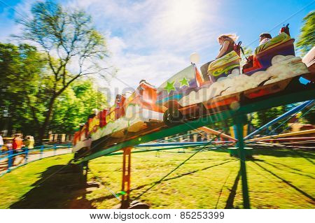 People Having Fun On Rollercoaster In The Park