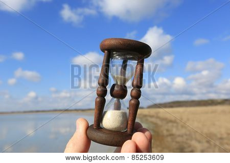 Hourglass in man hand on spring sky background