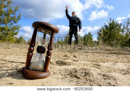 Hourglass on sand against man silhouette in pine forest
