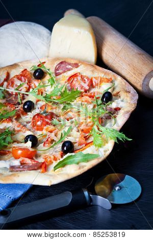 Pizza with dry cured ham and arugula