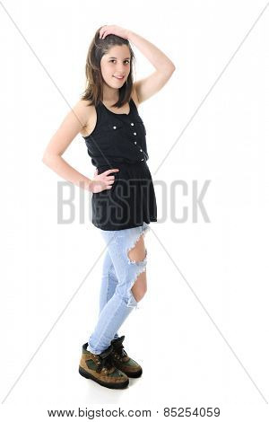 Full length image of a pretty teen brunette standing in her sleeveless black top, holey denim jeans and work boots.  On a white background.