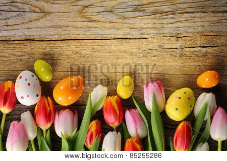 Easter eggs and tulips on grunge wood background