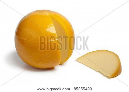Whole yellow round Edam cheese with a slice on white background