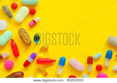 Many colorful pills isolated on yellow background