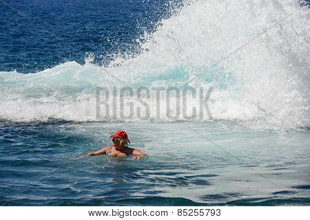 Stormy Splash Of Ocean Wave Behind The Senior Bather.