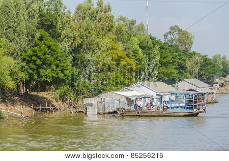 CHAU DOC, VIETNAM - JANUARY 2, 2013: Rural life in Mekong delta - Local people cross the Bassac River on small ferry boat