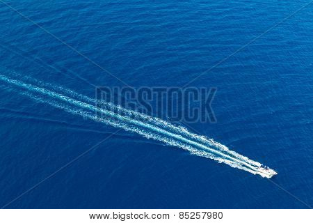 Boat surf foam aerial from prop wash in blue Majorca mediterranean sea