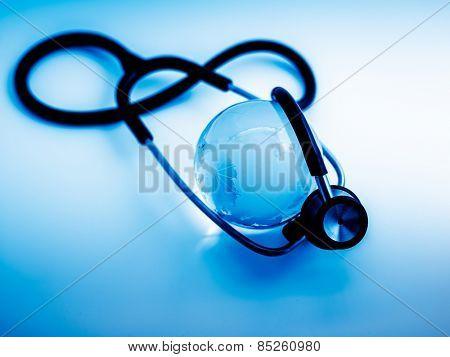 Global healthcare. Globe and stethoscope, studio shot.blue toned images.