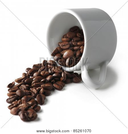 Spilled coffee beans from the cup isolated on white background
