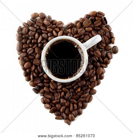 Cup of coffee on coffee beans shaped as a heart isolated on white background