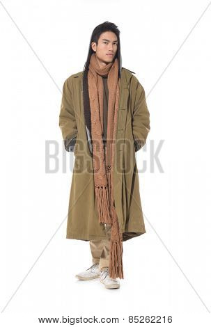 portrait of handsome stylish man in coat with scarf posing