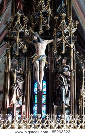 ST. WOLFGANG, AUSTRIA - DECEMBER 14: Crucifixion, Virgin Mary and St. John under the cross, main altar in Parish church in St. Wolfgang on Wolfgangsee in Austria on December 14, 2014.
