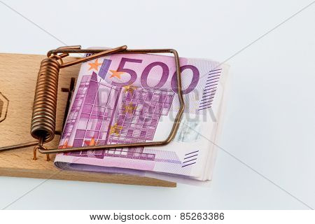 many euro banknotes in a mousetrap. symbolic photo for debt and debt in loans.