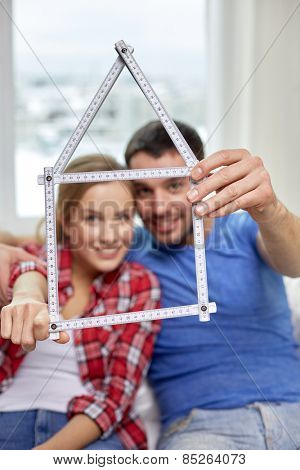 people, real estate and family concept - close up of happy couple looking through house shape made of ruler at home