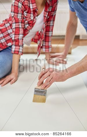 repair, renovation, building and people concept - close up of couple smearing wallpaper with glue on floor at home