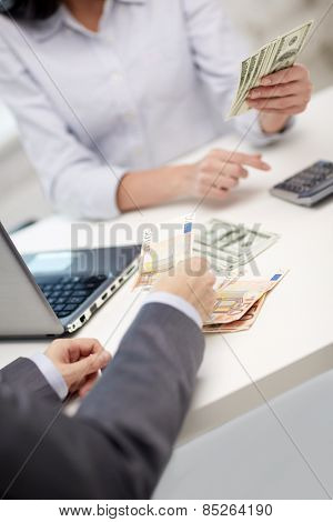 finances, currency, exchange rate, technology and people concept - close up of hands counting dollar and euro money with calculator