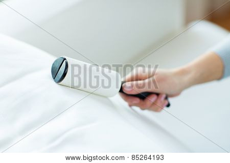 people, housework and housekeeping concept - close up of woman hand with sticky roller cleaning furniture textile