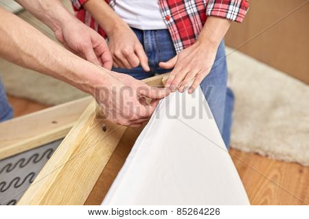 people, moving and furnishing concept - close up of couple assembling furniture at home