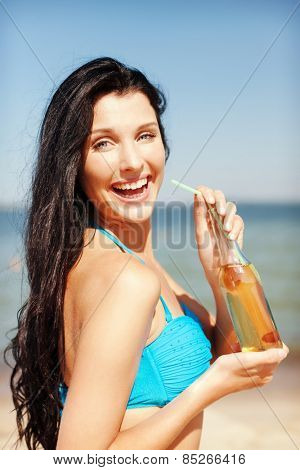 summer holidays, vacation and beach concept - girl with bottle of drink on the beach