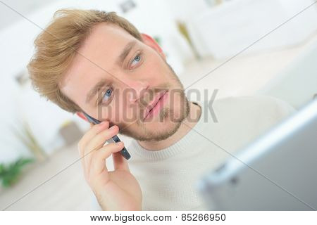 Man making a call whilst using his tablet computer