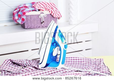 Electric iron and shirt on ironing board in room