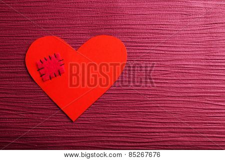 Patch on broken heart on colour background