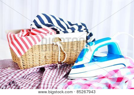 Iron with clothes on ironing board in room