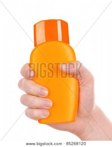 Bottle of suntan cream in female hand isolated on white