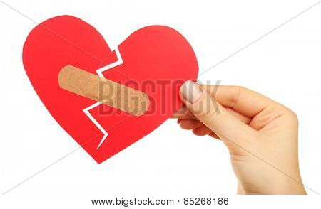 Female hand holding broken heart with plaster isolated on white