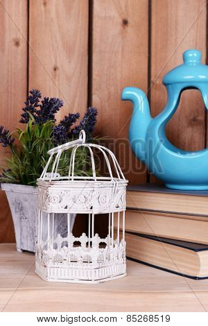 Interior design with decorative pot, cage, plant and stack of books on tabletop on wooden planks background