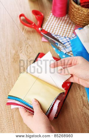 Colorful fabric samples in female hands and details for sewing on wooden table background