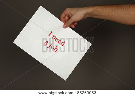 Sheet of paper with inscription I need a job in male hand on dark background