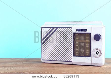 Retro radio on wooden table on blue background