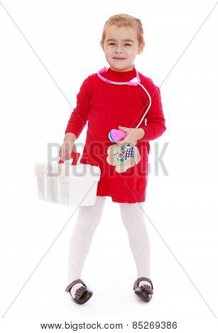 Positive little girl with a first aid kit in the hands of