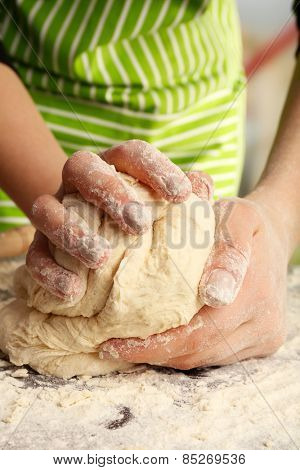 Making dough by female hands on wooden table and light blurred background