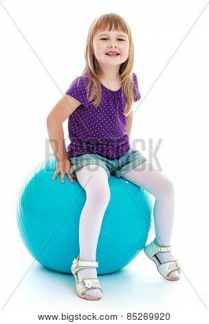 Very cute little girl sitting on a big ball sports.