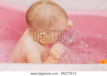 child bathes in a bathtub