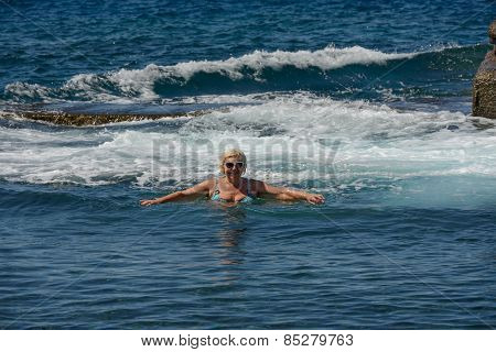 Senior Woman Is In The Foam Of The Ocean Surf.
