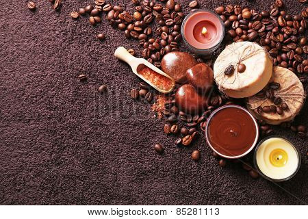 Composition of soap, chocolate in bowl and coffee beans on brown towel background