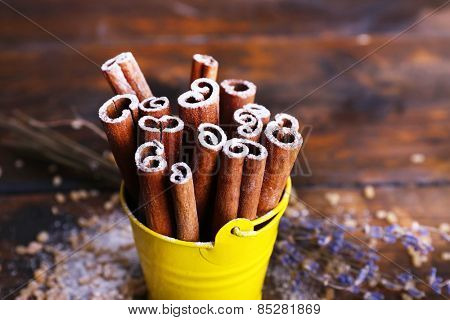 Cinnamon sticks with sugar and lavender on wooden table background