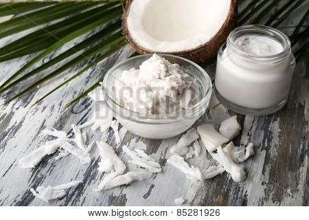 Coconut with coconut oil in bowl with jar of cosmetic cream on wooden background