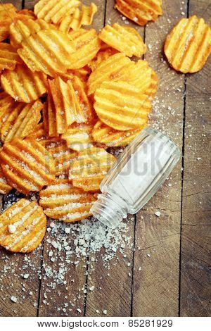Delicious potato chips with salt on wooden table close-up
